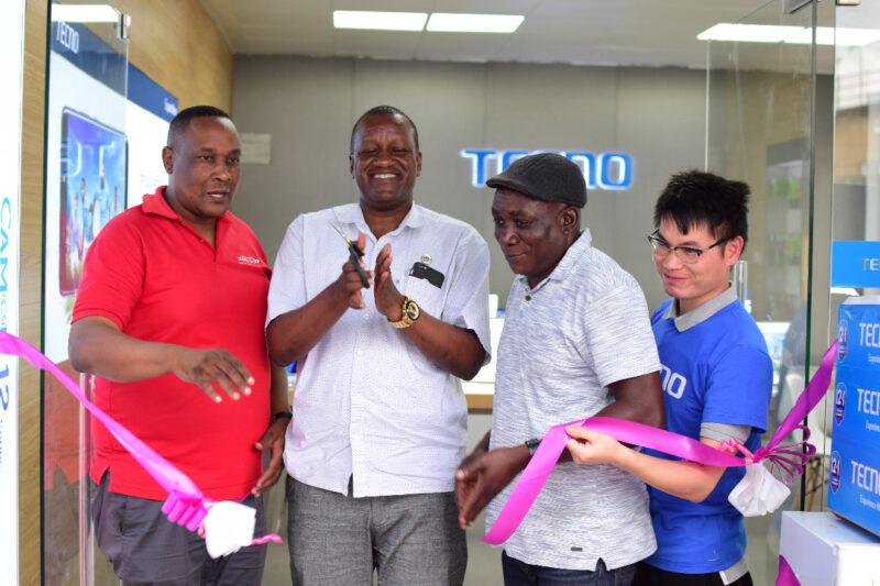 Bw. Benjamin Maneno Mwakilishi wa Mkurugenzi Jiji la Arusha akipiga makofi mara baada ya kukata utepe kuashiria uzinduzi wa dukala kisasa la TECNO.